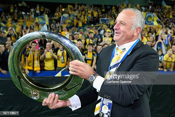 Mariners head coach Graham Arnold celebrates with the trophy after winning the ALeague 2013 Grand Final match between the Western Sydney Wanderers...