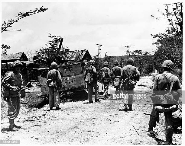 Marines advance through a ruined village on Tinian Island in pursuit of the Japanese