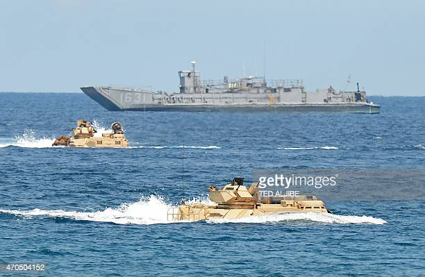 US Marines amphibious assault vehicles speed past a landing ship during an amphibious landing exercise on a beach at San Antonio in Zambales province...