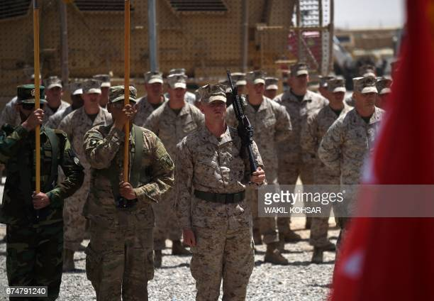 US Marines and Afghan National Army soldiers carry flags during a handover ceremony at Leatherneck Camp in Lashkar Gah in the Afghan province of...