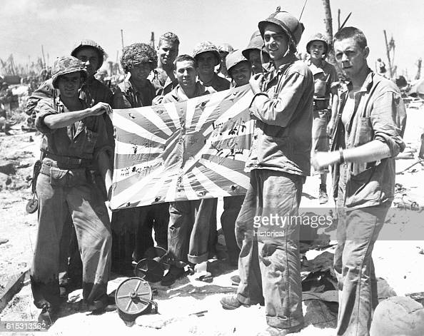 Marines and Coast Guard troops display a captured Japanese battle flag picked up during the American invasion of Engebi Island Bullet holes are...
