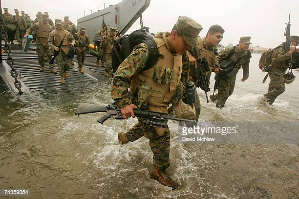 Marines and sailors of the 15th Marine Expeditionary Unit come ashore from a landing craft as they return from the war in Iraq on May 30 2007 at Camp...