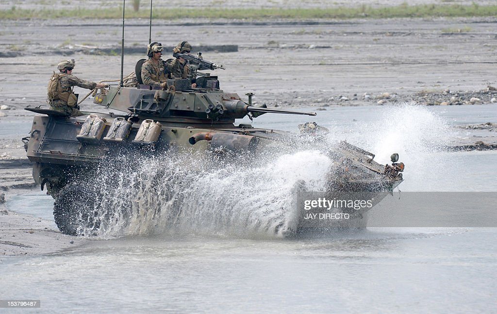 US Marines and their Philippine counterparts maneuver an amphibious armored personnel carrier through water at Crow Valley, Tarlac province in northern Philippines on October 9, 2012 to take part in the joint annual Philippine-US Amphibious Landing Exercises. The 10-day program will involve combined live fire exercises, aircraft displays, a helicopter raid as well as medical missions around Subic and in the western island of Palawan. The Philippines said on October 8 a former US naval base facing the South China Sea could play a key role as a hub for American ships as Washington moves to boost its presence in the Asia Pacific. AFP PHOTO / JAY DIRECTO