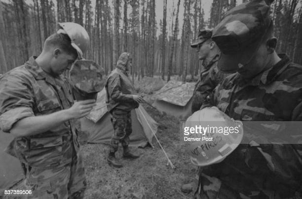 Marine Ronny McGough rt decorates his new fire helmet while fellowmarine Tim Schmidt left tries his on the Marines the new encampment in the rain at...
