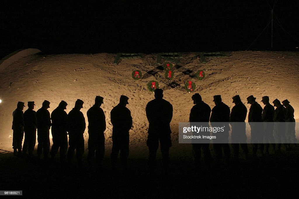 U.S. Marines bowing their heads in silence in honor of fallen comrades.