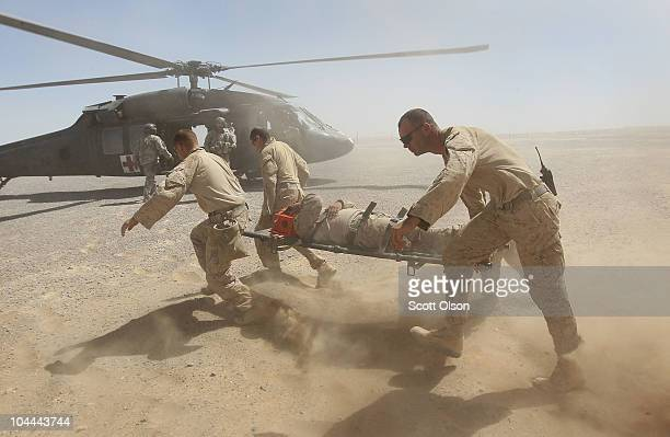 S Marines carry a fellow Marine Sgt Jorge Mazon of Mission Viejo CA to an Army MEDEVAC helicopter September 25 2010 near Marja Afghanistan Mazon was...