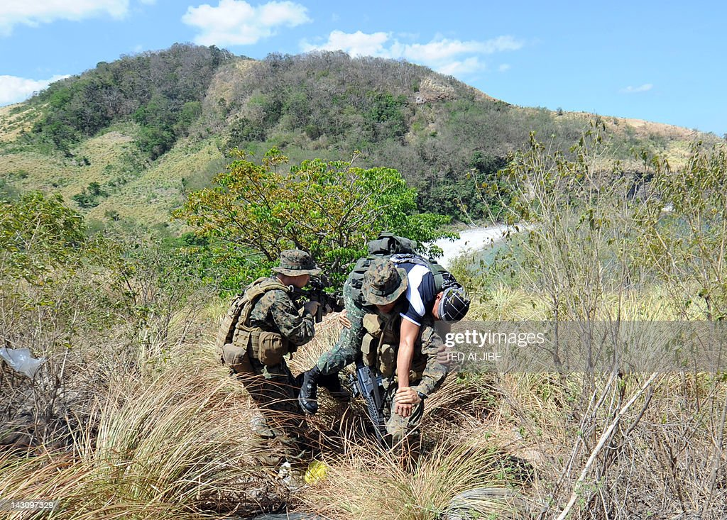 US marines carry a Philippine marine acting as a downed enemy during an ambush simulation as part of the twoweek PHUS military exercise inside the...