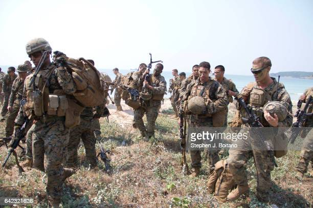 Marines carry gear on the beach head during the USThai joint military exercise titled 'Cobra Gold' on Hat Yao beach in Chonburi province eastern...