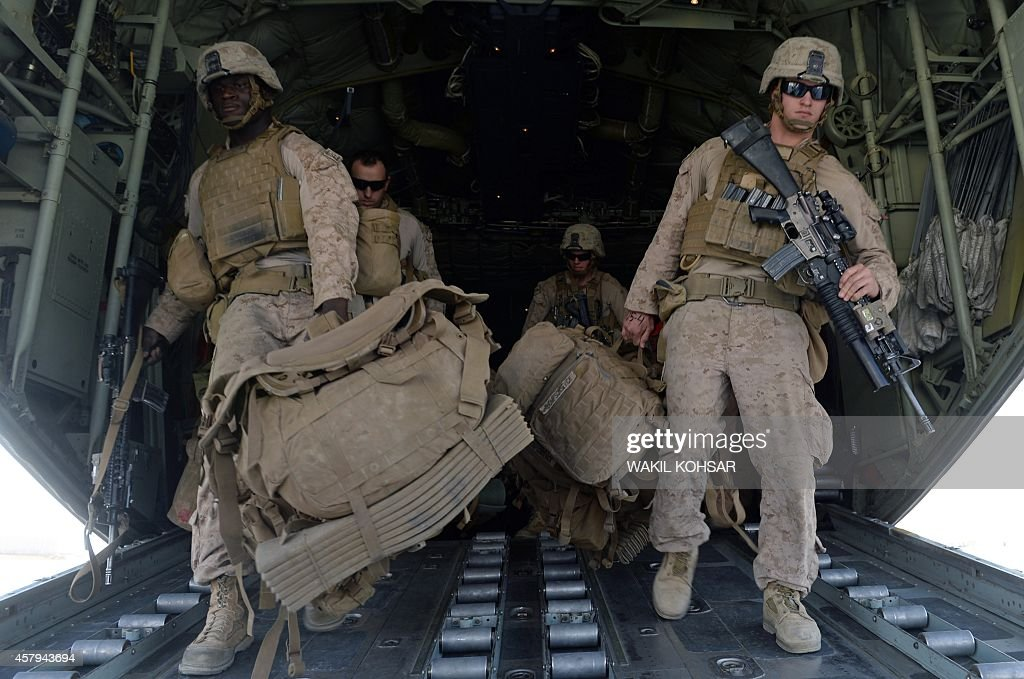 US Marines carry their gear after arriving in Kandahar on October 27 as British and US forces withdraw from the Camp BastionLeatherneck complex in...