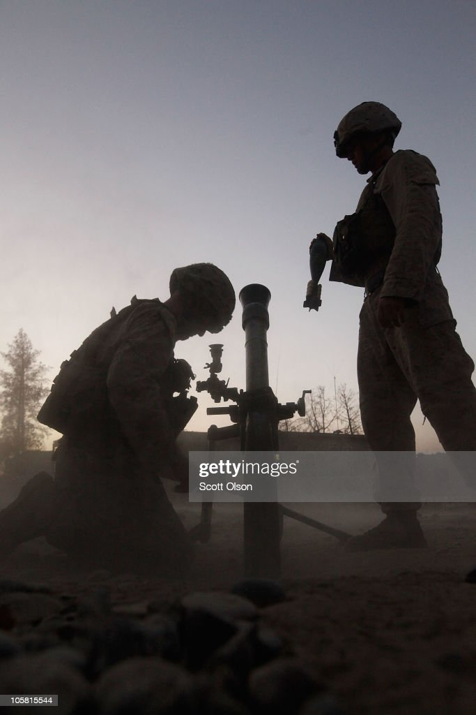U.S. Marines Cpl. Dave Needham from Fruita, CO and Cpl. Christopher Arnold of Crownsville, MD with India Battery, 3rd Battalion, 12th Marine Regiment prepare to fire mortar rounds at enemy positions at Forward Operating Base (FOB) Zeebrugge on October 20, 2010 in Kajaki, Afghanistan. The Marines of India Battery, 3rd Battalion, 12th Marine Regiment are responsible for securing the area near the Kajaki Dam on the Helmand River.