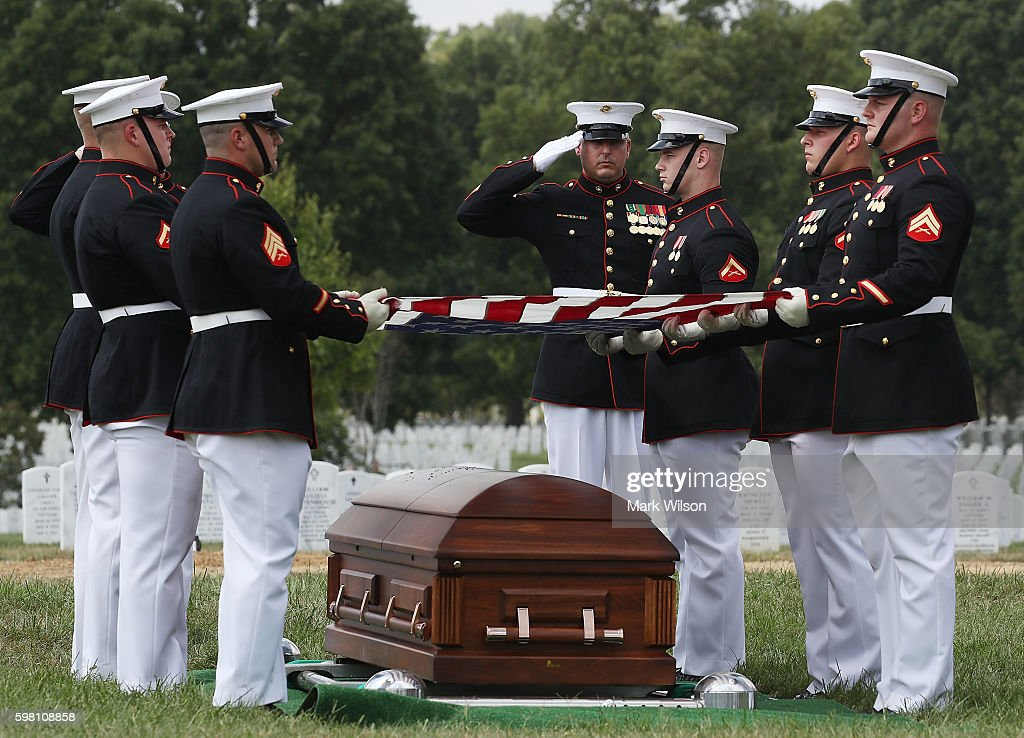 Marines fold an American flag over the remains of US Marine PFC Anthony Brozyna of Hartford CT during a full honor burial service at Arlington...