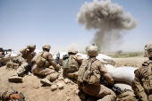 S Marines from 2nd Marine Expeditionary Brigade RCT 2nd Battalion 8th Marines Echo Co take cover as a 500 lb bomb explodes on a compound after the...