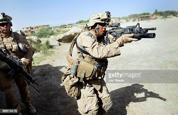 S Marines from 2nd Marine Expeditionary Brigade RCT 2nd Battalion 8th Marines Echo Co react to gunfire as they manuever to clear two buildings on...