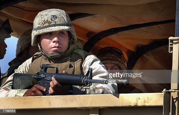 S Marines from 3rd Battallion 1st Marine Division ride in the back of a troop transport in route to February 1 2003 training at a base near the Iraqi...