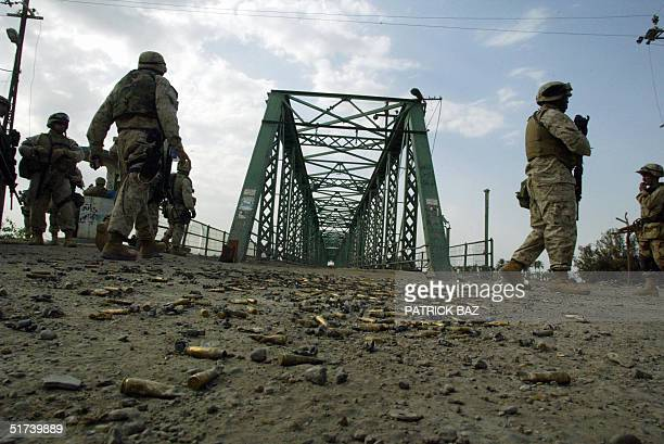 US marines from the 3/5 Lima company walk towards a the bridge that crosses the Euphrates River in the restive city of Fallujah14 November 2004 50...