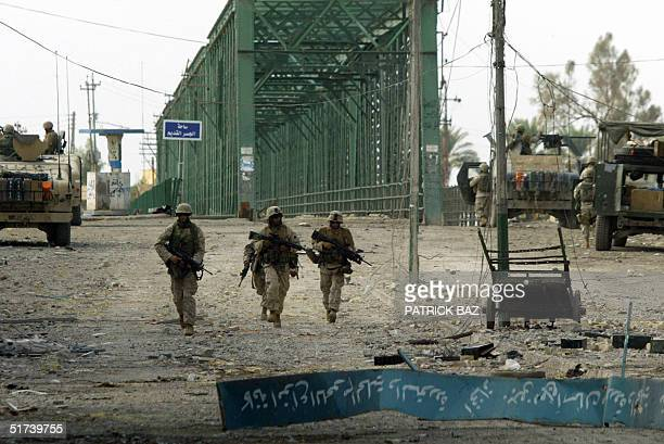 US marines from the 3/5 Lima company walks through the destruction past the 'old' bridge in the restive city of Fallujah 14 November 2004 50 kms west...