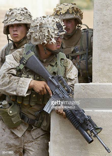US marines from the First Battalion Fifth Marines take cover from snipers during a raid southeast of Fallujah 50 km West of Baghdad 12 April 2004...