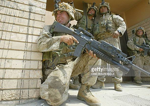 US marines from the First Battalion Fifth Marines take cover from snipers in the industrial area southeast of Fallujah 50 km West of Baghdad 12 April...