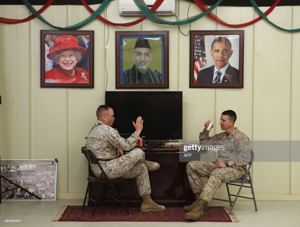 US Marines Lt Col Clint Benfield and Col Ben Watson talk underneath pictures of Queen Elizabeth Afghan President Hamid Karzai and President Barack...