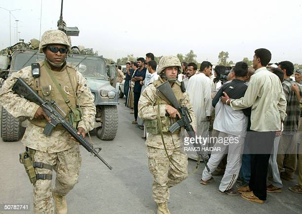 US marines make way for a convoy through a crowd Iraqis displaced from the city of Fallujah waiting for permission to return home 29 April 2004 AFP...