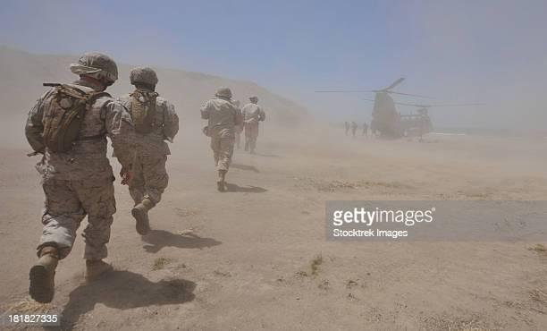 Marines move through a dust cloud toward a CH-46 Sea Knight.