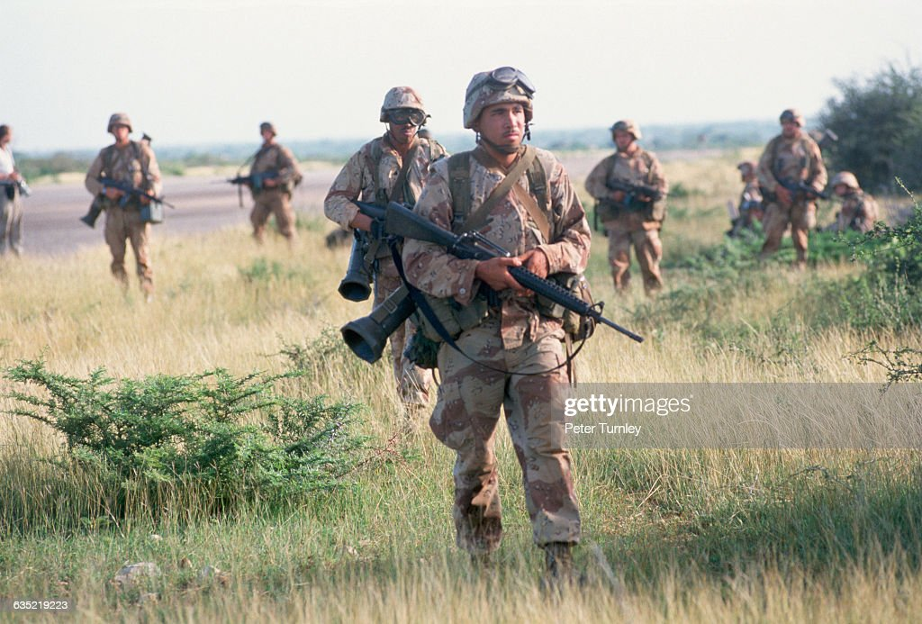 US Marines move through the grass after landing by helicopter at the Baidoa airport as part of 'Operation Restore Hope' in December of 1992 In the...