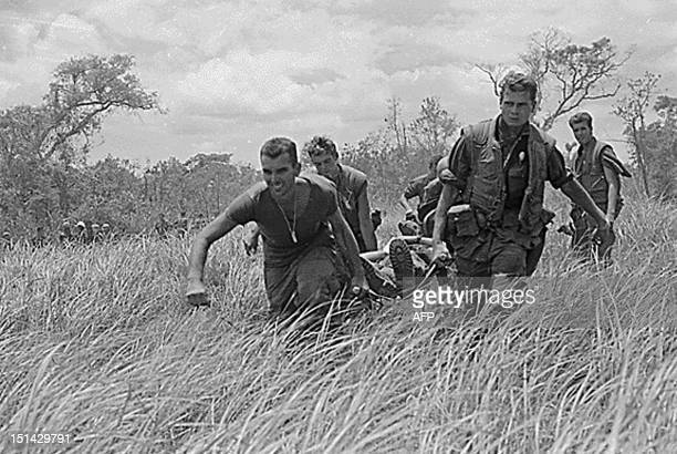 Marines of Company E 2nd Battalion 9th Marines carry one of their fellow Marines to the H34 while under heavy firefight with NVAs within the DMZ on...