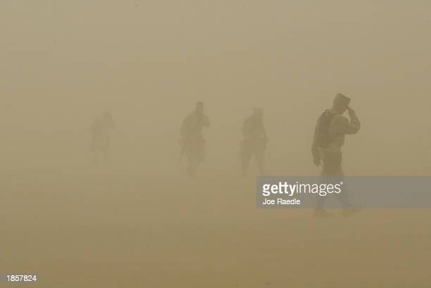S Marines of Task Force Tarawa walk through a dust storm at Camp Shoup March 19 2003 close to the Iraqi border in Kuwait The ultimatum by US...