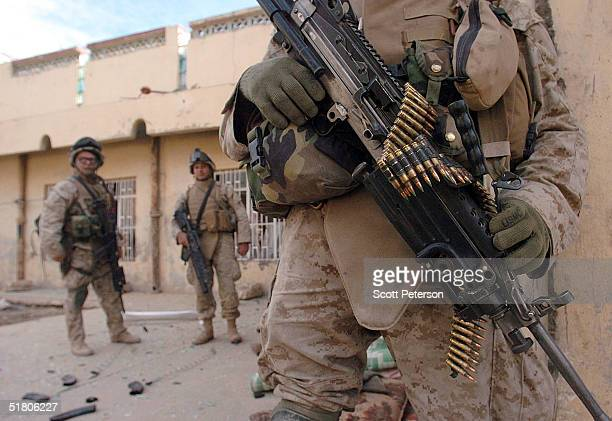 Marines of the 1st Battalion 3rd Marines stand guard after a battle with three insurgents while searching a house leaving one marine dead and three...