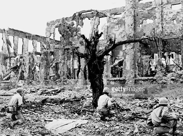 US Marines of the 1st Division crouch down as they attack a Japanese position in the ruins of Shuri Castle Shuri Okinawa Japan 1945 The castle was...