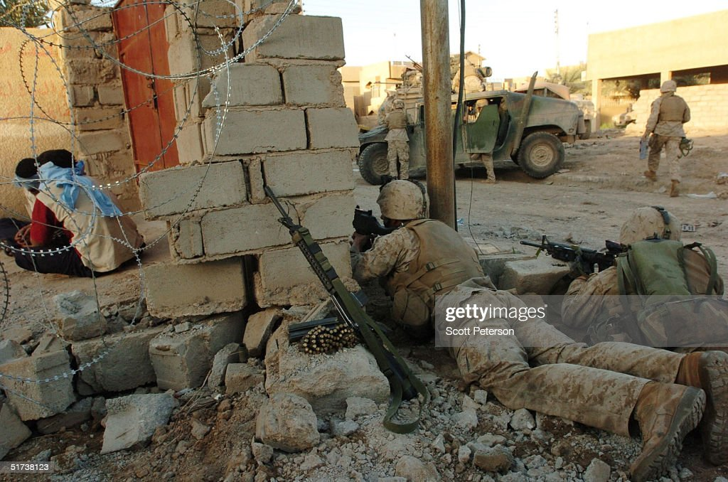 U.S. Marines of the 1st Light Armored Reconnaissance (LAR) company get caught up in a firefight while watching over two Iraqi detainees November 13, 2004 in Fallujah, Iraq. U.S. forces are pushing their offensive farther into Fallujah, battling remaining pockets of resistance.