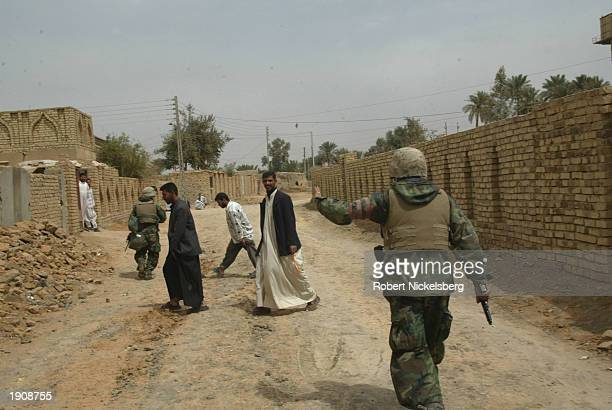 US Marines of the 1st Marine Division address Iraqi civilians March 30 2003 in Tahrir Iraq which is approximately 100 km south of Baghdad The Marines...
