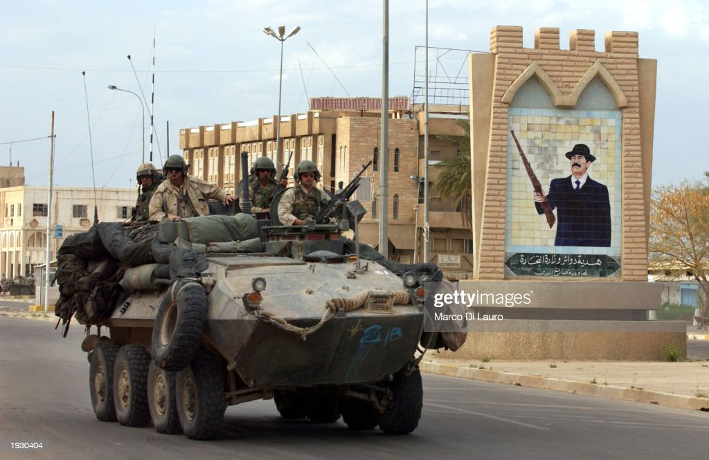U.S. Marines pass a Saddam Hussein portrait as they operate a light armored vehicle April 14, 2003 in the center of Tikrit which is located approximately 175 km (108 miles) north of Baghdad. U.S Marines made it to the center of the city and have encountered little resistance.