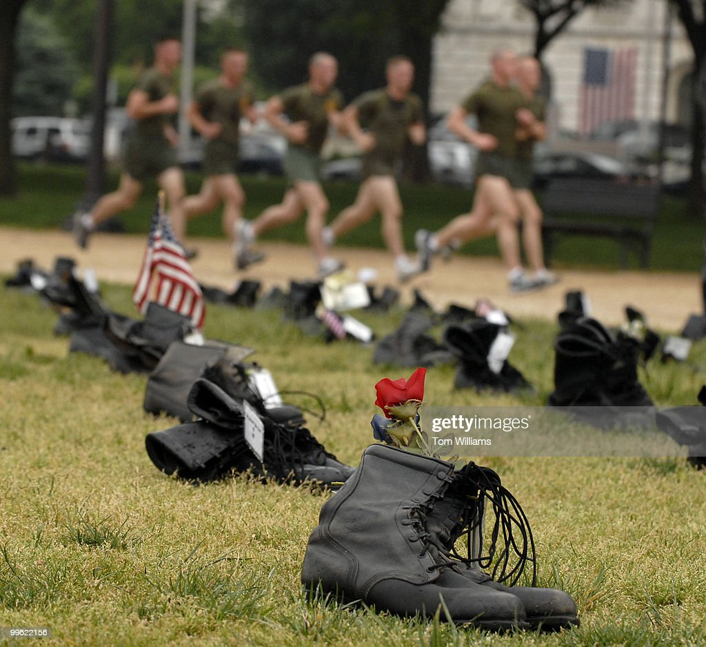 Marines run past pairs of boots that symbolize one of the 2432 US military personnel killed in Iraq The display is part of 'Eyes Wide Open The Human...