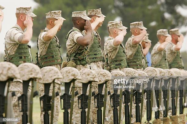 Marines salute behind memorials to their fallen comrades at a service memorializing the 420 soldiers sailors Marines and British soldiers who lost...