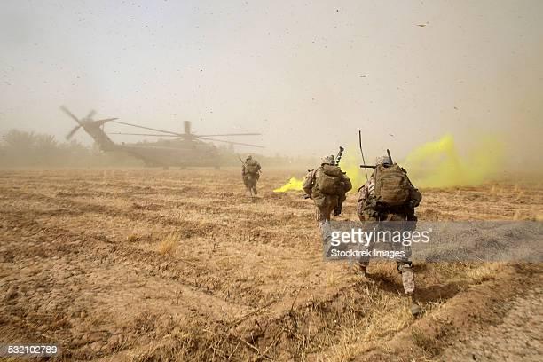 U.S. Marines sprint across a field to load onto a CH-53E Super Stallion.