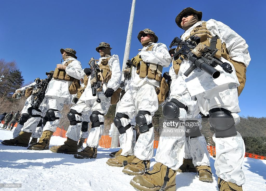 US Marines stand on a snowy hill during a joint winter drill in Pyeongchang, some 180 kilometers east of Seoul, on February 7, 2013. Marines from South Korea and the United States took part in a military winter drills, which began on February 4 and run through February 22, to test their limits in extreme conditions.