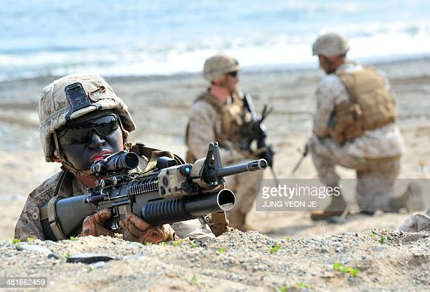 US Marines take a position during a joint landing operation by US and South Korean Marines in Pohang 270 kms southeast of Seoul on March 31 2014...
