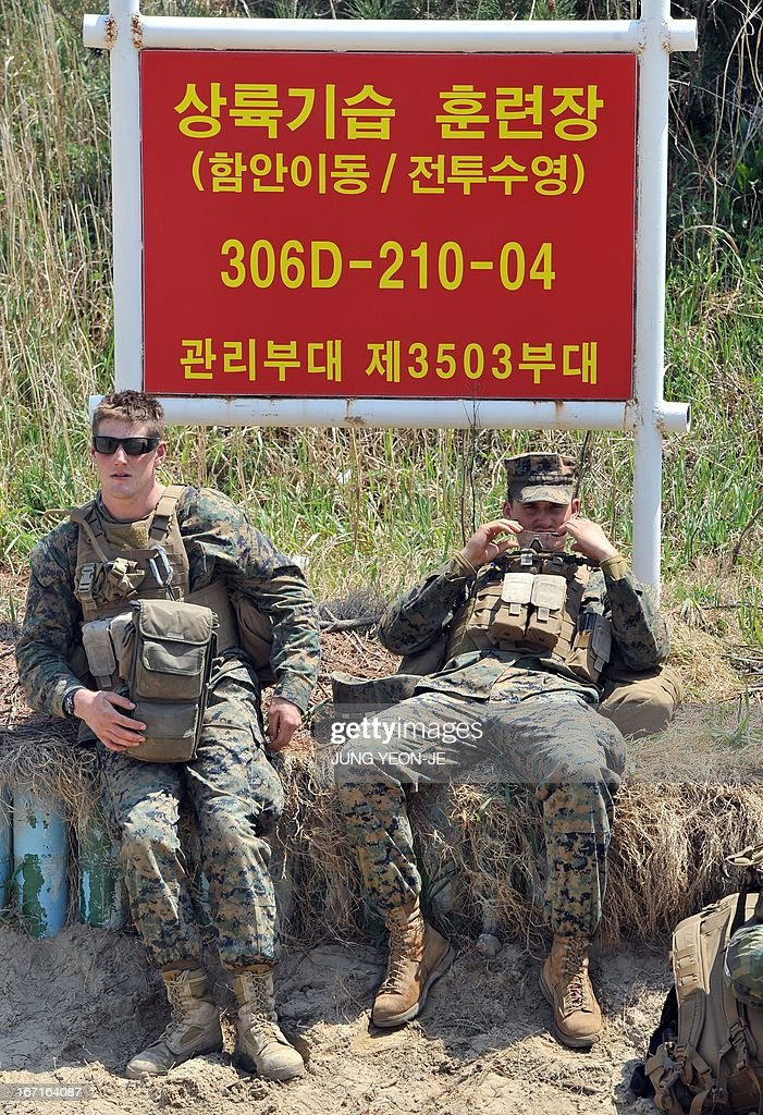 US Marines take a rest under a red board reading 'landing training area' at a beach during the Combined Joint Logistics Over the Shore (CJLOTS) exercise in Pohang, 260 kms southeast of Seoul, on April 22, 2013. The wait for North Korea's expected missile test, which has kept South Korean and US forces on heightened alert for the past two weeks, may stretch to July, the South's defence ministry said on April 22.