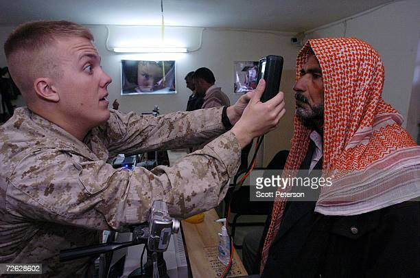 S Marines take retina scans and fingerprints of Iraqi residents of Fallujah Iraq for biometric cards required of all locals in the city on November...