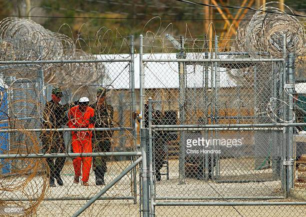 Marines transport a detainee behind layers of fencing and razorwire in Camp XRay February 6 2002 in Guantanamo Bay Cuba Some of the 156 AlQaeda or...