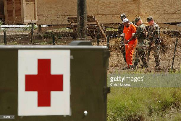 Marines transport a detainee in Camp XRay as a military medic vehicle sits in the foreground February 6 2002 in Guantanamo Bay Cuba Many of the 156...