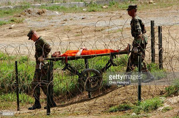 S Marines transport a detainee on a gurney at Camp XRay February 6 2002 in Guantanamo Bay Cuba Many of the 156 Al Qaeda or Taliban detainees are...