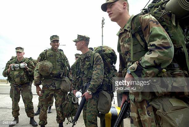 US Marines wait to board a hired High Speed Vessel to take them from the South Korean sea port of Pohang 24 June 2003 back to their base in Okinawa...
