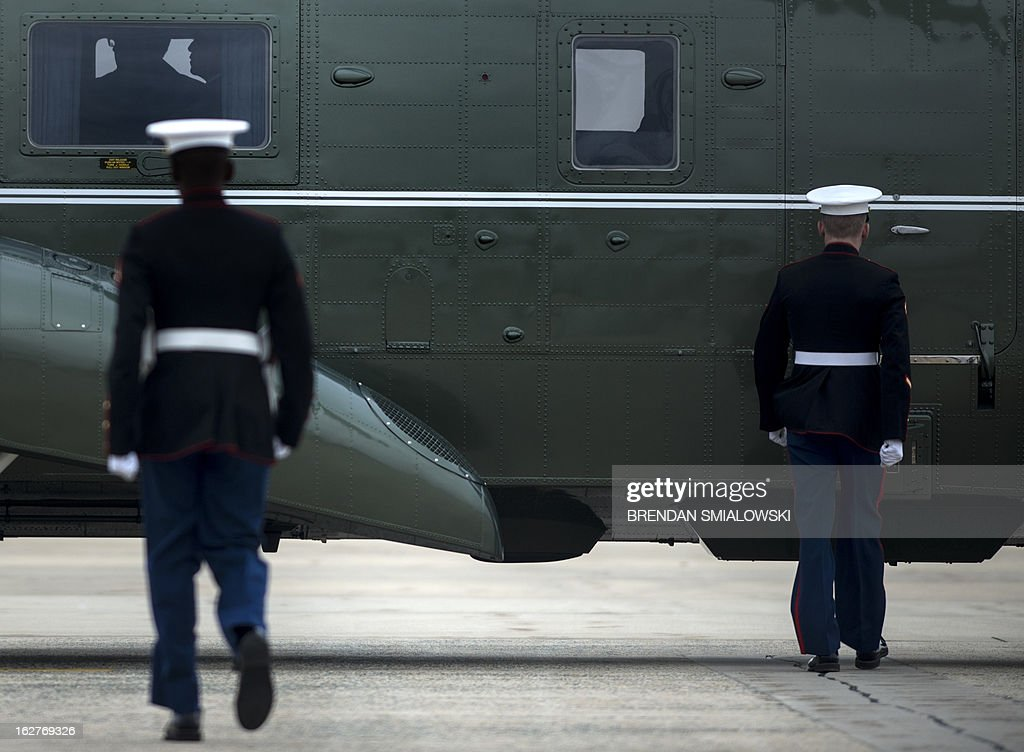 Marines walk toward Marine One with US President Barack Obama aboard as he arrives at Andrews Air Force Base on February 26, 2013 in Maryland. Obama is traveling to speak about the effects economic sequester in Newport News, Virginia. AFP PHOTO/Brendan SMIALOWSKI