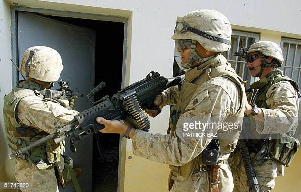 Marines with a Civil Affairs unit perpare to storm a water facility in the devastated city of Fallujah west of Baghdad 15 November 2004 Smoke...