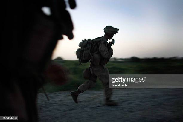 S Marines with the 2nd Marine Expeditionary Brigade RCT 2nd Battalion 8th Marines Echo Co rush down a road after seeing suspicious activity near...