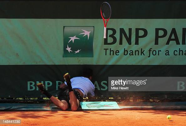 Marinko Matosevic of Australia falls into the back fence of court 11 after chasing a ball during the men's doubles first round match between Ashley...