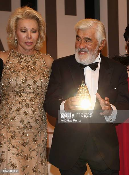 Mario Adorf holds up his award as Ute Ohoven looks on during the 21st UNESCO Charity Gala 2012 on October 27 2012 in Dusseldorf Germany