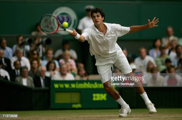 Mario Ancic of Croatia returns a forehand to Roger Federer of Switzerland during day nine of the Wimbledon Lawn Tennis Championships at the All...